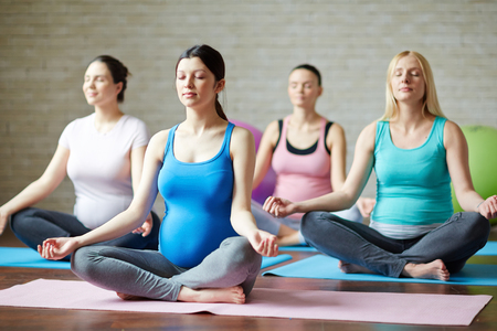 Several pregnant women practicing yoga in gym Banco de Imagens