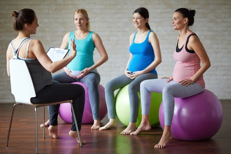 childbearing: Young pregnant women listening to their fitness trainer Stock Photo