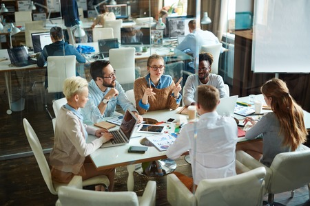 gathered: Group of modern employees gathered for meeting in office Stock Photo