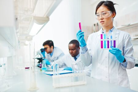 Group of international scientist working with chemicals