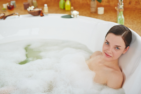 lying in bathtub: Young woman relaxing in bath Stock Photo