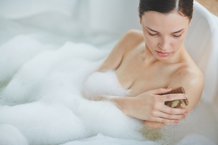 lying in bathtub: Young woman taking bath and cleaning skin