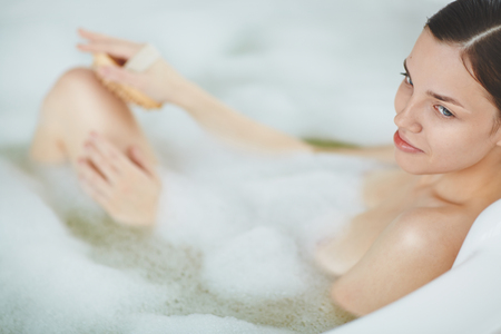 Young woman taking bath with soap sud Stock Photo