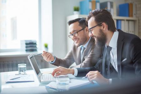 colegas masculinos sonriendo mientras mira la pantalla del portátil Foto de archivo