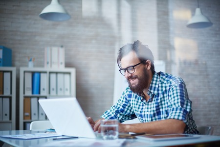 man with laptop: Young man working in office alone and smiling