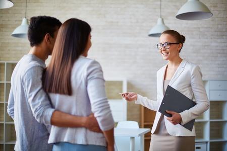 Žena realitní kanceláře mluvit s mladou rodinu
