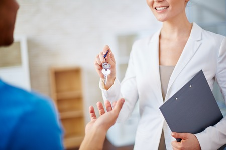 agente comercial: Mujer del agente inmobiliario que da claves a un hombre Foto de archivo