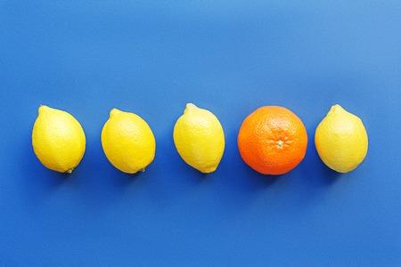 limonero: Fila de limones con una naranja