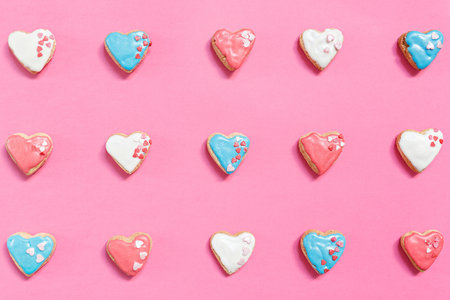 romantic love: Pink background with rows of homemade heart-shaped pastries