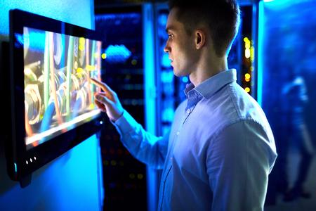 El hombre usando la pantalla táctil en la universidad o un museo