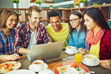 young group: Group of young people sitting at cafe and networking Stock Photo