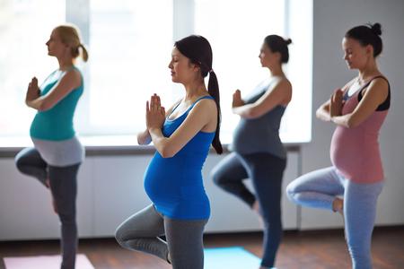 Las mujeres embarazadas que ejercita en la clase de yoga