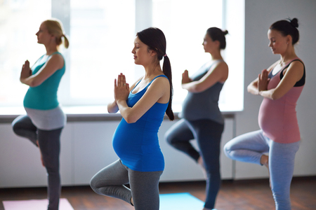 Pregnant women exercising in yoga class