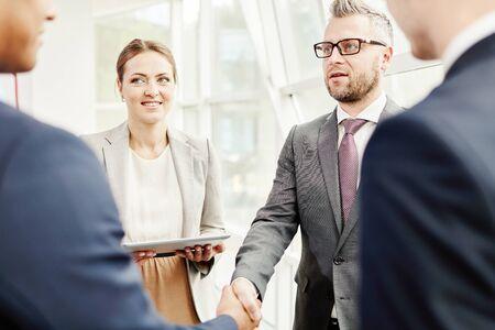 handshaking: Happy colleagues looking at businessmen handshaking after striking deal
