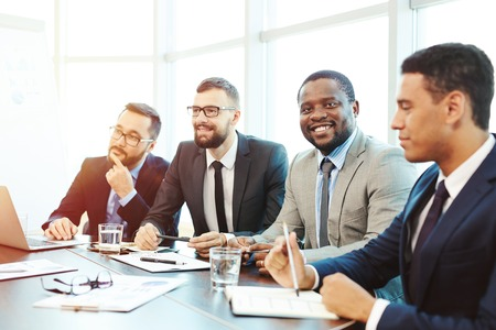 employees: Smiling businessman looking at camera among colleagues