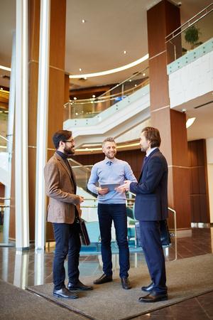 empleados trabajando: Tres empleados se comunican con éxito en el salón del centro de la oficina moderna