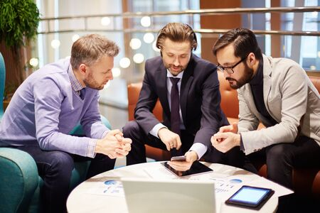 young businessman: Young confident employees looking at smartphone display at meeting Stock Photo