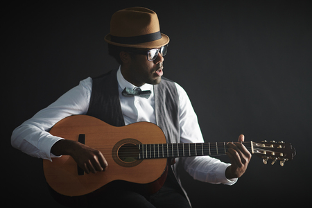 one person only: Young African musician playing guitar and singing