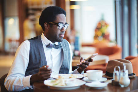 man eating: Elegant young man with smartphone eating in cafe Stock Photo