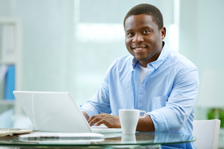 businesspeople: Young businessman looking at camera while typing in office