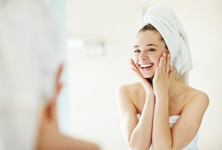 after bath: Happy girl looking at her face in mirror after bath Stock Photo