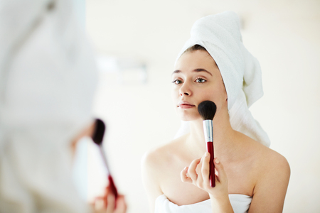 face powder: Pretty girl applying face powder in front of mirror