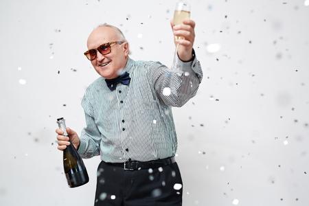 Felice l'uomo anziano con la bottiglia e flute di champagne guardando la fotocamera a festa Archivio Fotografico - 55419416