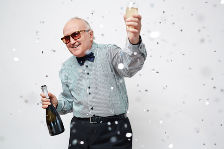 Happy senior man with bottle and flute of champagne looking at camera at party Фото со стока