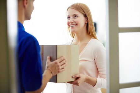 package: Pretty woman receiving package from delivery man Stock Photo
