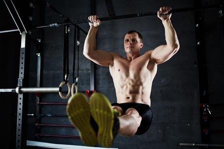 pullups: Muscular man doing pull-ups in gym