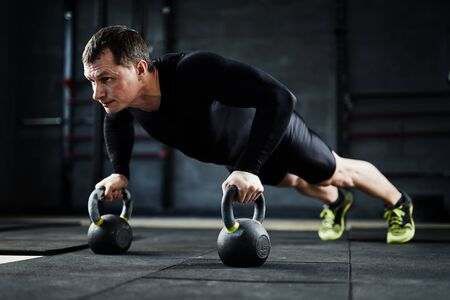 activewear: Strong man doing push-ups with kettles