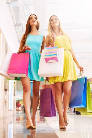 after shopping: Satisfied shopaholics going down mall after shopping Stock Photo