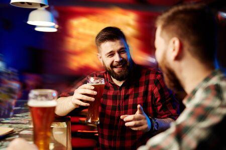 vasos de cerveza: Hombre joven feliz con la cerveza y su amigo hablando en el pub