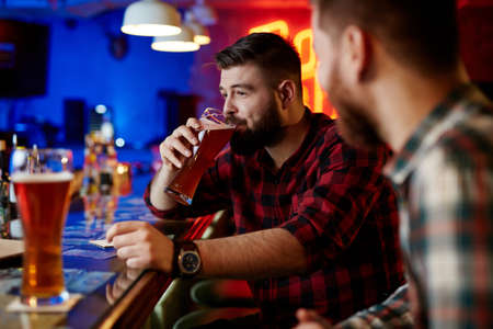 near beer: Young man drinking cool beer in pub with his friend near by Stock Photo