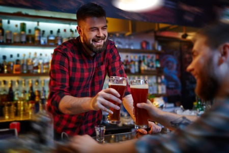 barman: Happy barman and client clinking with glasses of beer in pub Stock Photo