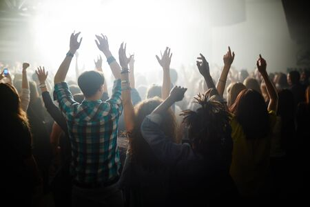 crowd: Crowd of ecstatic fans with raised hands dancing by songs of their favorite modern singer at live concert Stock Photo