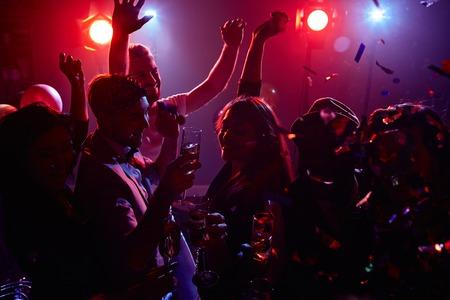 dancing club: Joyful friends with champagne dancing in disco club