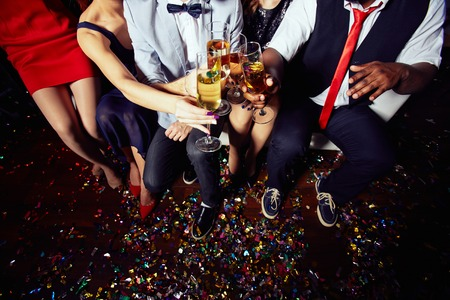 elegant party: Group of friends in smart clothes clinking with flutes of champagne