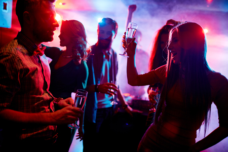 ecstatic: Ecstatic friends with champagne dancing in night club