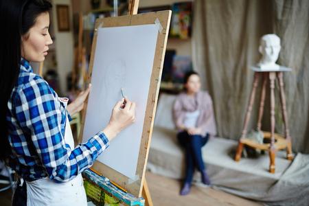 paper craft: joven estudiante dibujar la cara de la muchacha con el lápiz en el taller Foto de archivo