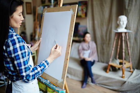 creative artist: Young student drawing face of girl with pencil in workshop
