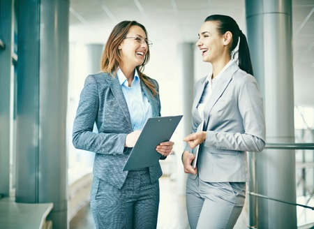 women business: Two successful businesswomen talking and laughing Stock Photo