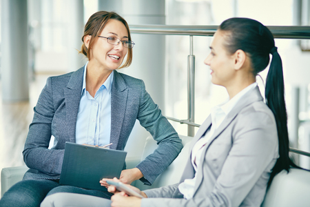 colleague: Businesswoman talking to her female colleague Stock Photo