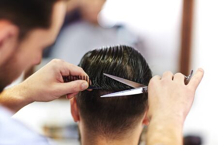 man haircut: Modern hairdresser with scissors serving his client Stock Photo
