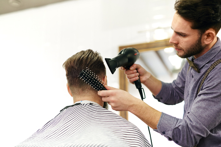 hairbrush: Modern hairdresser styling hair of client with hairbrush and hair-dryer