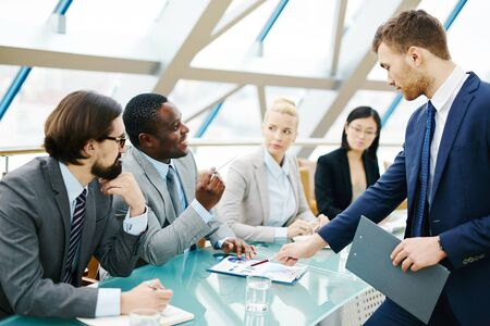 discussing: Multi-ethnic managers discussing data at meeting Stock Photo