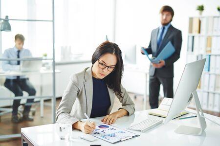 Jeune travailleur de bureau d'analyse des données financières devant l'ordinateur Banque d'images