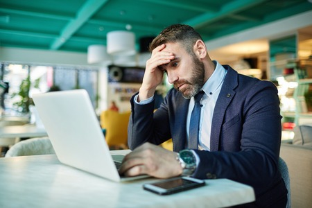 Mooie zakenman die op laptop scherm kijkt Stockfoto