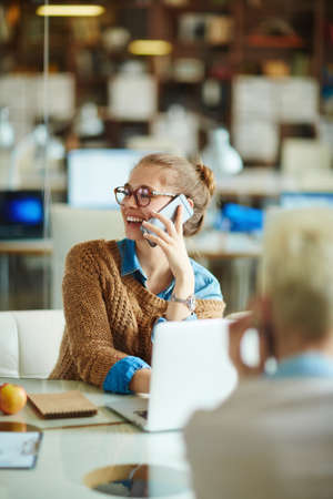 casual office: Contemporary businesswoman talking on cellphone at workplace