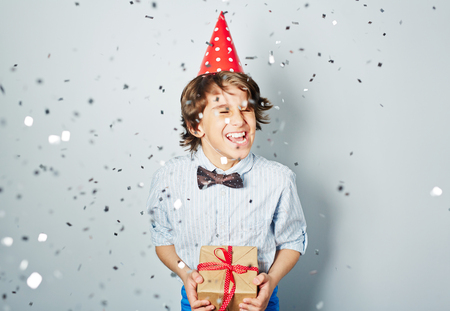 ecstatic: Ecstatic boy in birthday cap holding packed gift Stock Photo
